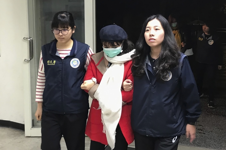 In this photo taken on Dec. 28, 2018, immigration officers escort a detained Vietnamese national in New Taipei City, Taiwan. Taiwanese immigration authorities have found 24 Vietnamese and are searching for 124 others who left their tour groups after arriving in December on tourist visas. (National Immigration Agency via AP)