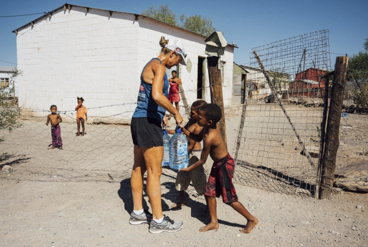 In this Monday, Dec. 31, 2018 photo supplied by Flux Communications, Mina Guli, an Australian activist seeking to highlight global water shortages, gives water to young children, in Beaufort West, South Africa. Guli is struggling to complete 100 marathons in 100 days across the world. Now in South Africa, 48-year-old Guli is more than half-way through the punishing project, but she's injured and a spokeswoman said Wednesday, Jan. 2, 2019 that the advocate will walk the rest of the marathons. (Kelvin Trautman, Flux Communications via AP)
