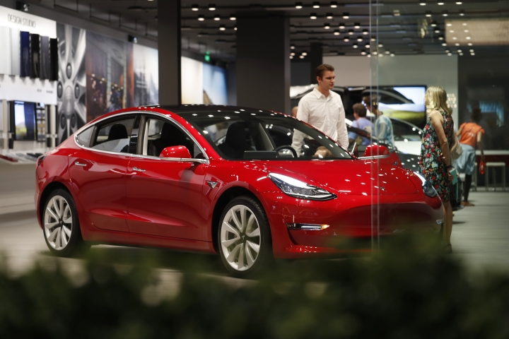 FILE- In this July 6, 2018, file photo, a prospective customer confer with sales associate as a Model 3 sits on display in a Tesla showroom in the Cherry Creek Mall in Denver. On Tuesday, Jan. 1, 2019, the federal credit for Tesla buyers dropped from $7,500 to $3,750. It will gradually be phased out this year. (AP Photo/David Zalubowski, File)