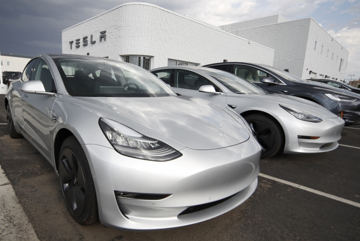 FILE- In this July 8, 2018, photo 2018 Model 3 sedans sit on display outside a Tesla showroom in Littleton, Colo. On Tuesday, Jan. 1, 2019, the federal credit for Tesla buyers dropped from $7,500 to $3,750. It will gradually be phased out this year. (AP Photo/David Zalubowski, File)