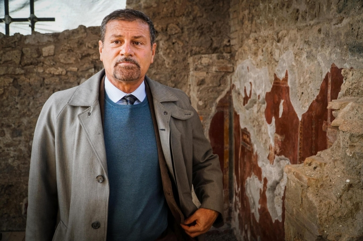 The general manager of the archaeological park of Pompeii, Massimo Osanna, stands by a fresco at the Schola Armaturarum building in Pompeii, Italy, Thursday, Jan. 3, 2019. A 2,000-year-old building where gladiators trained in ancient Pompeii is now open to visitors, eight years after its collapse following rainfall. The Pompeii archaeological site said the public can visit the Schola Armaturarum on Thursdays and that restoration experts will explain how they painstakingly restored frescoes inside the building. (Cesare Abbate/ANSA via AP)