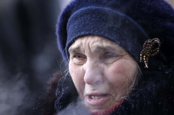A woman reacts during prayers at the scene of the collapsed apartment building in Magnitogorsk, a city of 400,000 people, about 1,400 kilometers (870 miles) southeast of Moscow, Russia, Wednesday, Jan. 2, 2019. The building's pre-dawn collapse on Monday came after an explosion that was believed to have been caused by a gas leak. (AP Photo/Maxim Shmakov)