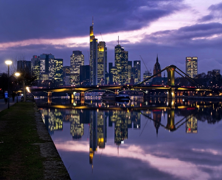 The buildings of the banking district are reflected on the plain surface of the river Main in Frankfurt, Germany, Thursday, Jan. 3, 2019. (AP Photo/Michael Probst)