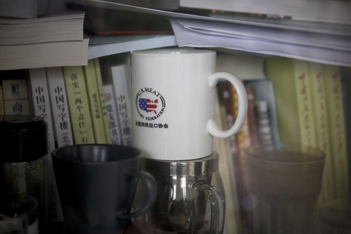 FILE- In this Dec. 3, 2018, photo, a cup baring the logo of U.S. Meat Export Federation is placed inside a bookshelf at an office in the Beijing International Club. The Trump administration and China are facing growing pressure to blink in their six-month stare-down over trade because of jittery markets and portents of economic weakness. The longer their trade war lasts, the longer companies and consumers will feel the pain of higher-priced imports and exports. (AP Photo/Andy Wong, File)