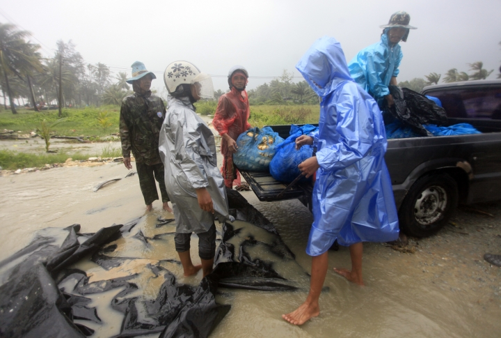 Locals prepare for the approaching Tropical Storm Pabuk, Friday, Jan. 4, 2019, in Pak Phanang, in the southern province of Nakhon Si Thammarat, southern Thailand. Rain, winds and surging seawater are striking southern Thailand as a strengthening tropical storm nears coastal villages and popular tourist resorts. (AP Photo/Sumeth Panpetch)