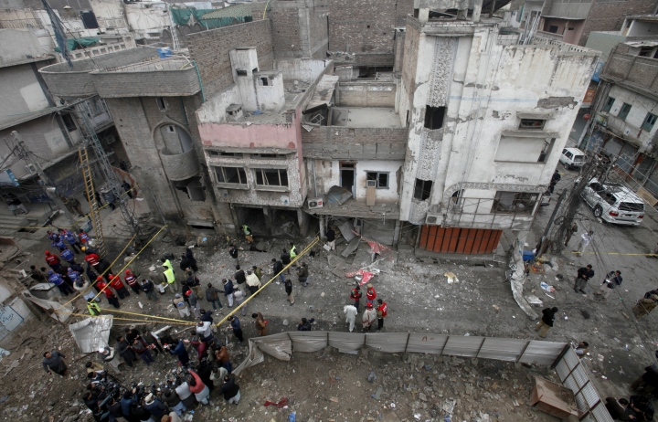 Pakistani police officers and rescue workers gather at the site of bomb blast in Peshawar, Pakistan, Saturday, Jan. 5, 2019. Pakistani police say a car bomb exploded in a Peshawar neighborhood wounding three people and damaging several shops. (AP Photo/Mohammad Sajjad)