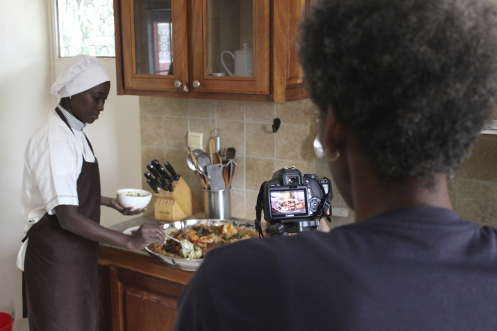 In this Nov. 24, 2018, photo, Filmmaker Tuleka Prah, right, films chef Touty Sarr , as she prepares a plate of thiebou dieune, a traditional Senegalese dish of spiced rice, inside a kitchen in Ngaparou, Senegal. In the quiet hours before lunch, two women worked side by side in an airy kitchen. One, a chef, cleaned fresh red snapper filets with a sharp knife. The other, a filmmaker, pointed her camera into a large pot of simmering vegetables. (AP Photo/Amelia Nierenberg)