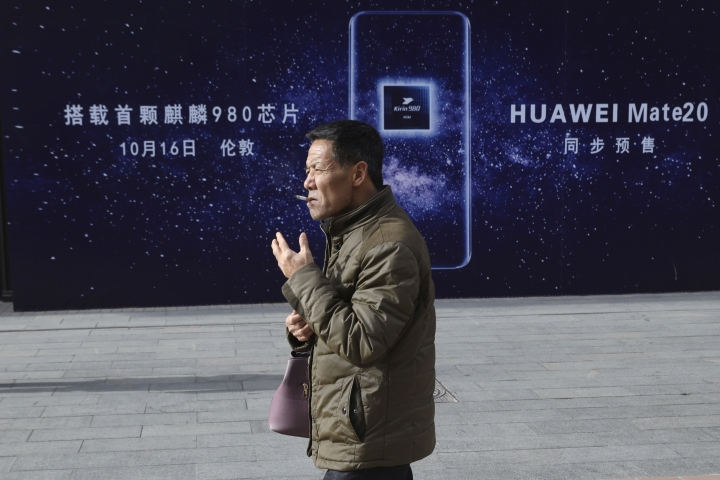 A man smokes as he pass by an advertisement for Huawei products in Beijing Monday, Jan. 7, 2019. Huawei Technologies Ltd. unveiled a processor chip Monday for data centers and cloud computing in a bid by the biggest global maker of telecom equipment to expand into new markets despite Western warnings the company might be a security risk. (AP Photo/Ng Han Guan)