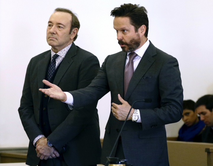 Actor Kevin Spacey stands in district court as his attorney Alan Jackson, right, addresses the judge during arraignment on a charge of indecent assault and battery on Monday, Jan. 7, 2019, in Nantucket, Mass. The Oscar-winning actor is accused of groping the teenage son of a former Boston TV anchor in 2016 in the crowded bar at the Club Car in Nantucket. (Nicole Harnishfeger/The Inquirer and Mirror via AP, Pool)