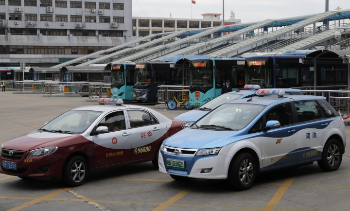 In this Monday, Jan. 7, 2019, photo, a new electric-powered taxi, right, and a gasoline-powered taxi are seen in Shenzhen city, south China's Guangdong province. One of China's major cities has reached an environmental milestone, an almost all electric-powered taxi fleet. The high-tech hub of Shenzhen in southern China announced at the start of this year that 99 percent of the 21,689 taxis operating in the city were electric. (AP Photo/Vincent Yu)