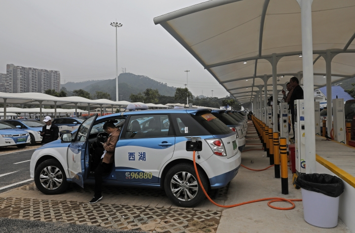 In this Monday, Jan. 7, 2019, photo, new electric-powered taxi are charged at a public charging station in Shenzhen city, south China's Guangdong province. One of China's major cities has reached an environmental milestone, an almost all electric-powered taxi fleet. The high-tech hub of Shenzhen in southern China announced at the start of this year that 99 percent of the 21,689 taxis operating in the city were electric. (AP Photo/Vincent Yu)