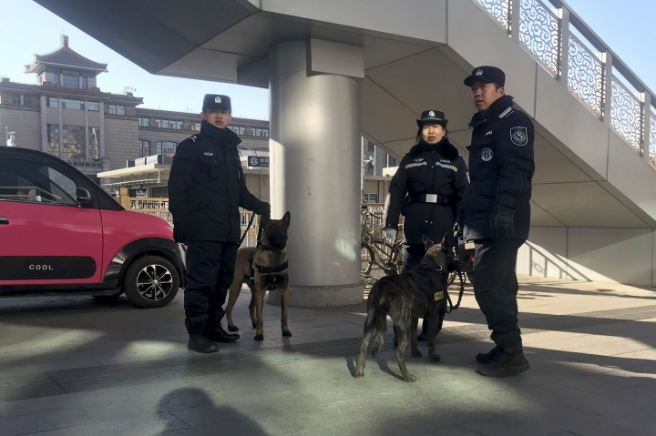Police officers and police dogs sniff parked vehicles outside a train station before the arrival of North Korean leader Kim Jong Un in Beijing, China, Tuesday, Jan. 8, 2019. Kim is making a four-day trip to China, the North's state media reported Tuesday, in what's likely an effort by Kim to coordinate with his only major ally ahead of a summit with U.S. President Donald Trump that could happen early this year. (AP Photo/Ng Han Guan)