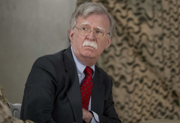 FILE - In this Dec. 26, 2018 file photo, National Security Adviser John Bolton attends a meeting with President Donald Trump and senior military leadership at Al Asad Air Base, Iraq. On Monday, Jan. 7, 2018, a Syrian Kurdish official said Syria's Kurds are awaiting clarifications from the U.S. over America's withdrawal plans following comments made by Bolton which appeared to contradict earlier comments by President Donald Trump. Bolton, on a visit to Israel Sunday, said U.S. troops will not leave northeastern Syria until IS militants are defeated and American-allied Kurdish fighters are protected. (AP Photo/Andrew Harnik, File)
