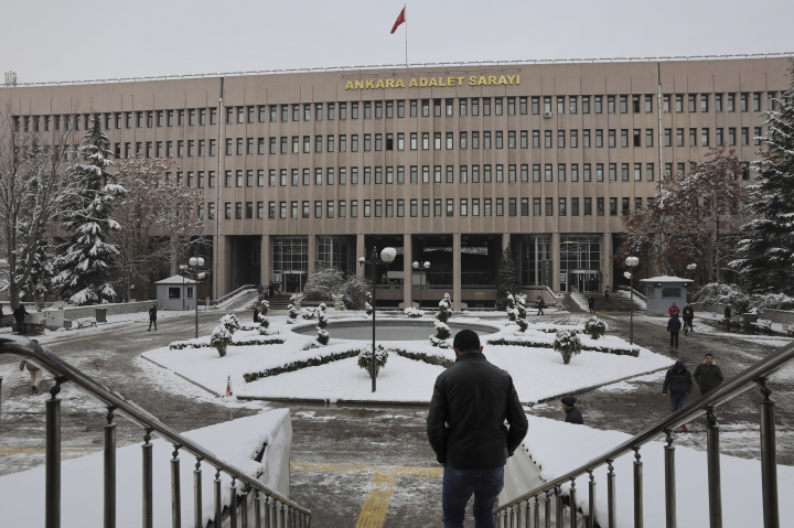 A man walks towards a court in Ankara, Turkey, on Tuesday, Jan. 8, 2019, where a trial has opened against 28 people accused of involvement in the 2016 killing of Russia's ambassador to Turkey. An off-duty police officer fatally shot Andrei Karlov at a photo exhibition in Ankara on Dec. 19, 2016. The officer was later shot dead at the scene by police. (AP Photo/Ali Unal)