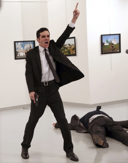 CAPTION CORRECTS THE TRIAL INFO FILE - In this Monday, Dec. 19, 2016 file photo Mevlut Mert Altintas, an off-duty policeman, shouts after shooting Andrei Karlov, right, the Russian ambassador to Turkey, at an art gallery in Ankara, Turkey. Altintas was killed by police shortly afterwards. A trial against 28 people accused of involvement in Karlov's killing begins in Ankara on Tuesday, Jan. 8, 2019. (AP Photo/Burhan Ozbilici, File)