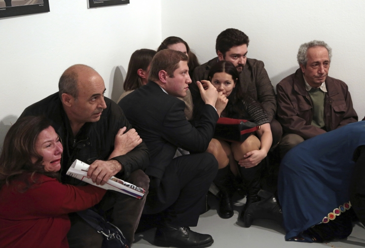 CAPTION CORRECTS THE TRIAL INFO -FILE - In this Monday, Dec. 19, 2016 file photo, gallery goers cower after off-duty policeman Mevlut Mert Altintas shot and killed Andrei Karlov, the Russian ambassador to Turkey, at an art gallery in Ankara, Turkey. Altintas was killed by police shortly afterwards. A trial against 28 people accused of involvement in Karlov's killing begins in Ankara on Tuesday, Jan. 8, 2019. (AP Photo/Burhan Ozbilici, File)