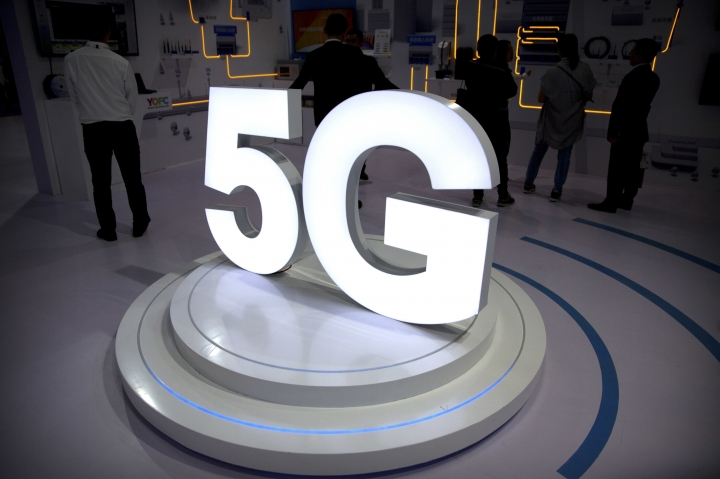 """FILE- In this Sept. 26, 2018, file photo visitors stand near a 5G logo at a display the PT Expo in Beijing. AT&T has drawn ridicule by relabeling the network used by some of its phones as """"5G E"""" to signal that the next-generation wireless network is here. Problem is, phones capable of connecting to 5G aren't coming for another few months, and a national 5G network won't be deployed until 2020 or 2021. (AP Photo/Mark Schiefelbein, File)"""