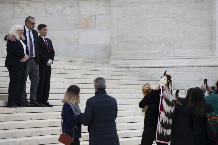 Attorney Kyle Ann Gray, left, Clayvin Herrera, and attorney Frederick Liu pose for pictures on the steps of the Supreme Court, Tuesday, Jan. 8, 2019, in Washington. The U.S. Supreme is reviewing a case in which Clayvin Herrera, a Crow tribal member and former tribal game warden from Montana, is asserting his right under a 150-year-old treaty with the U.S. government to hunt elk in the Bighorn National Forest in Wyoming. (AP Photo/Alex Brandon)