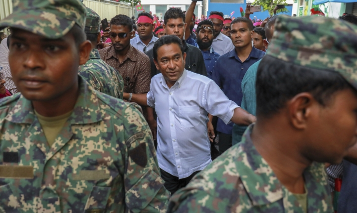 FILE- In this Feb. 3, 2018, file photo, Maldivian President Yameen Abdul Gayoom, center, surrounded by his body guards arrives to address his supporters in Male, Maldives. The Maldives' government has asked citizens to report information regarding allegations of corruption and abuse of power during the tenure of the strongman leader defeated in elections last year. The request, in a statement from the president's office on Wednesday, Jan. 9, came a day after police questioned Gayoom over alleged illegal financial transactions for a third time. (AP Photo/Mohamed Sharuhaan, File)