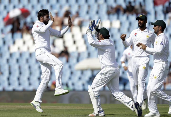 Pakistan's bowler Mohammad Amir, left, celebrates with teammates after dismissing South Africa's batsman Hashim Amla for 8 runs on day one of the cricket test match between South Africa and Pakistan at Centurion Park in Pretoria, South Africa, Wednesday, Dec. 26, 2018. (AP Photo/Themba Hadebe)