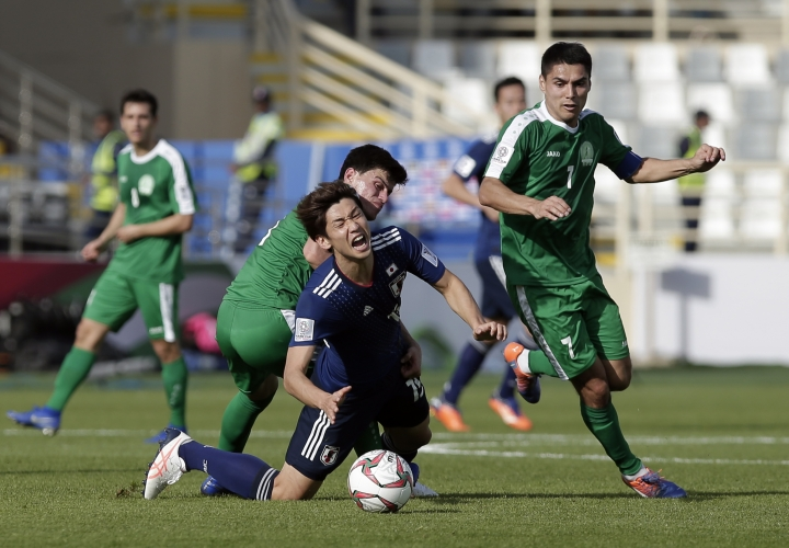 Japan's forward Yuya Osako, center front, duels for the ball with Turkmenistan's midfielder Resul Hojayev during the AFC Asian Cup group F soccer match between Japan and Turkmenistan at Al Nahyan Stadium in Abu Dhabi, United Arab Emirates, Wednesday, Jan. 9, 2019. (AP Photo/Nariman El-Mofty)