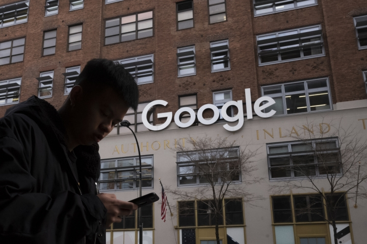 "FILE - In this file photo dated Monday, Dec. 17, 2018, a man using a mobile phone walks past Google offices in New York, USA. The European Court of Justice's advocate general released a preliminary opinion Thursday Jan 10, 2019, saying Google does not have to extend ""right to be forgotten"" rules to its search engines globally, in the case involving the U.S. tech giant and France's data privacy regulator. (AP Photo/Mark Lennihan, FILE)"