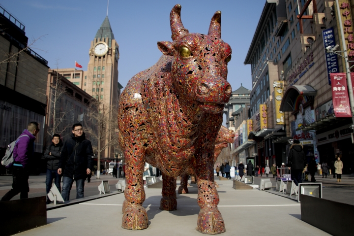 """People walk by bulls sculptures titled """"Five Bulls Gathering Fortune"""" on display at the Wangfujing shopping district in Beijing, Thursday, Jan. 10, 2019. Uncertainty over the outcome of China-U.S. trade talks is casting a pall over Asian markets as both sides kept quiet about what lies ahead. (AP Photo/Andy Wong)"""