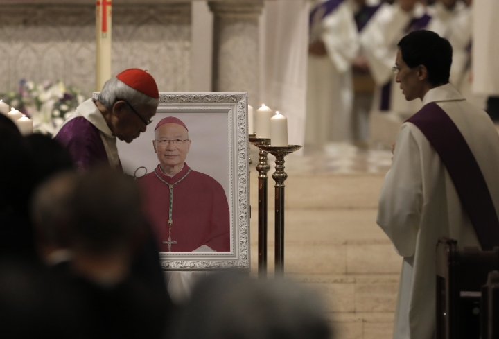 Cardinal Joseph Zen, left, a vocal opponent of attempts by Beijing and the Vatican at rapprochement, walks past the picture of Bishop Michael Yeung as he presides a vigil Mass in Hong Kong, Thursday, Jan. 10, 2019. Hong Kong Catholics mourned the loss of their bishop with a Mass on Thursday night amid a low-key struggle among clergy over reconciliation between the Vatican and Beijing. Bishop Michael Yeung died last week from liver failure after less than two years as the head of the diocese of more than 500,000 Catholics in the semi-autonomous Chinese territory. (AP Photo/Vincent Yu)