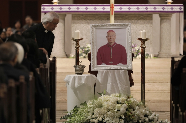 Parishioners pay their last respects next to the picture of Bishop Michael Yeung at a vigil Mass in Hong Kong, Thursday, Jan. 10, 2019. Hong Kong Catholics mourned the loss of their bishop with a Mass on Thursday night amid a low-key struggle among clergy over reconciliation between the Vatican and Beijing. Bishop Michael Yeung died last week from liver failure after less than two years as the head of the diocese of more than 500,000 Catholics in the semi-autonomous Chinese territory. (AP Photo/Vincent Yu)
