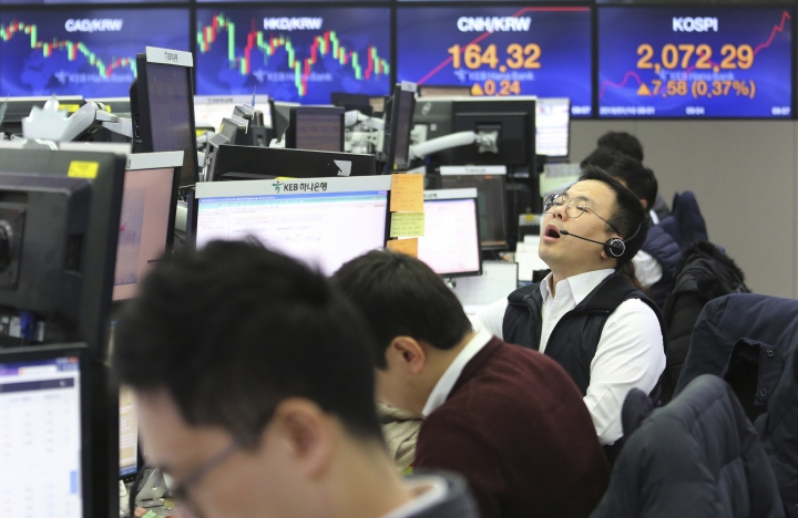 A currency trader shouts at the foreign exchange dealing room of the KEB Hana Bank headquarters in Seoul, South Korea, Thursday, Jan. 10, 2019. Asian markets were mostly lower Thursday as U.S. and Chinese officials wrapped up three days of talks in Beijing without significant breakthroughs. (AP Photo/Ahn Young-joon)