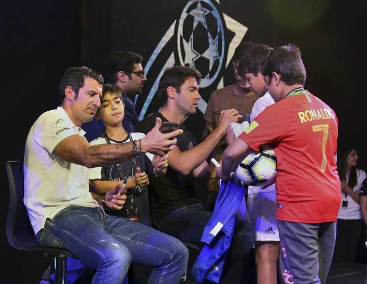 Portugal soccer player Luis Figo, left, takes a selfie with a boy while Brazilian soccer player Ricardo Kaka, center, signs autographs during a ceremony in Karachi, Pakistan, Thursday, Jan. 10, 2019. Soccer greats Figo and Kaka arrived in Pakistan to launch World Soccer Stars event in a country known for his passion about game of cricket. (AP Photo/Fareed Khan)