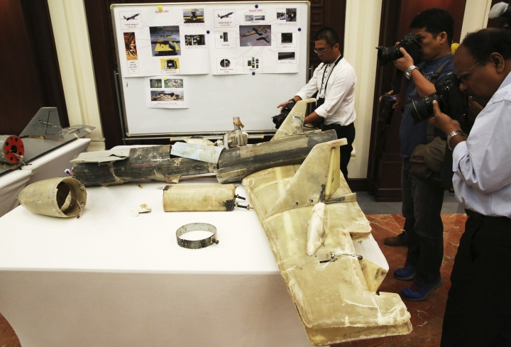 FILE - In this June 19, 2018 file photo, photographers take pictures of what U.A.E. officials described as an Iranian Qasef drone captured on the battlefield in Yemen during a news conference in Abu Dhabi, United Arab Emirates. A deadly bomb-laden drone flown by Yemen's Houthi rebels flew into a military parade on Thursday, Jan. 10, 2019, outside of the southern port city of Aden, targeting high-ranking military officials in Yemen's internationally recognized government. The brazen attack threatens U.N.-brokered peace efforts to end the yearslong war tearing at the Arab world's poorest nation. (AP Photo/Jon Gambrell, File)