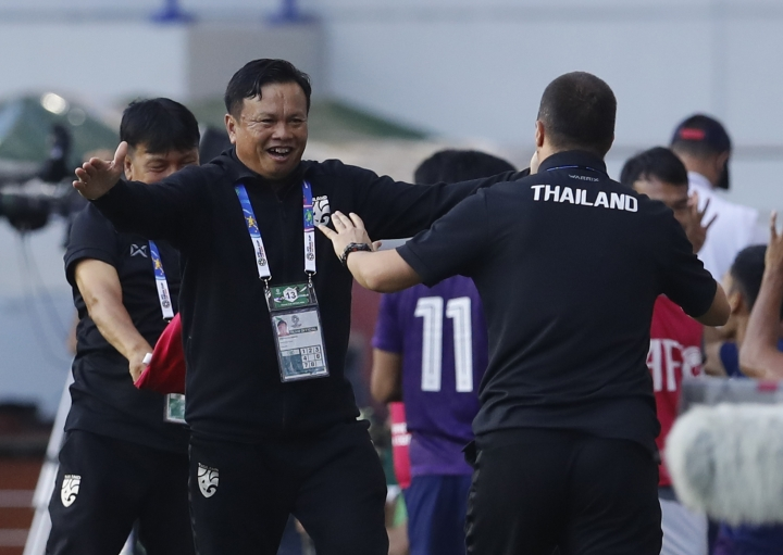 CORRECTS NAME OF THAILAND'S HEAD COACH TO SIRISAK YODYARDTHAI -Thailand's head coach Sirisak Yodyardthai, left, celebrates with a team member, right, after his team beat Bahrain, during the AFC Asian Cup group A soccer match between Bahrain and Thailand at Al Maktoum Stadium in Dubai, United Arab Emirates, Thursday, Jan. 10, 2019. (AP Photo/Hassan Ammar)