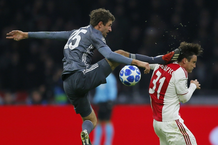 FILE - In this Wednesday, Dec. 12, 2018 file photo, Ajax's Nicolas Tagliafico, right, is fouled by Bayern's Thomas Mueller during the Champions League group E soccer match between Ajax and FC Bayern Munich at the Johan Cruyff Arena in Amsterdam, Netherlands. Bayern Munich forward Thomas Mueller has been banned for both games against Liverpool in the Champions League round of 16. UEFA says its disciplinary panel imposed a two-game ban for Mueller's red card after a bad tackle against Ajax last month. (AP Photo/Peter Dejong, File)