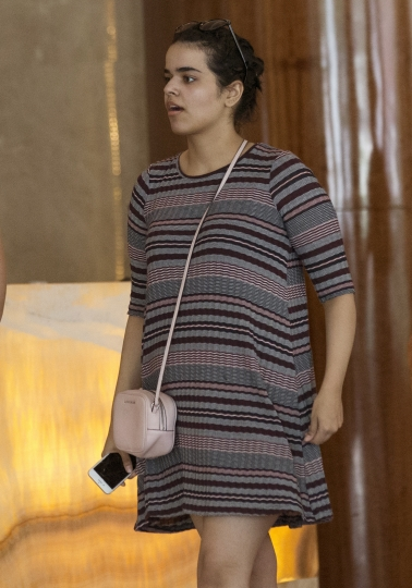 Rahaf Mohammed Alqunun holds a mobile phone in Bangkok, Thailand, Friday, Jan. 11, 2019. Alqunun, the 18-year old Saudi woman who fled her family to seek asylum, remains in Thailand under the care of the U.N. refugee agency as she awaits a decision by a third country to accept her as a refugee. (AP Photo/Sakchai Lalit)