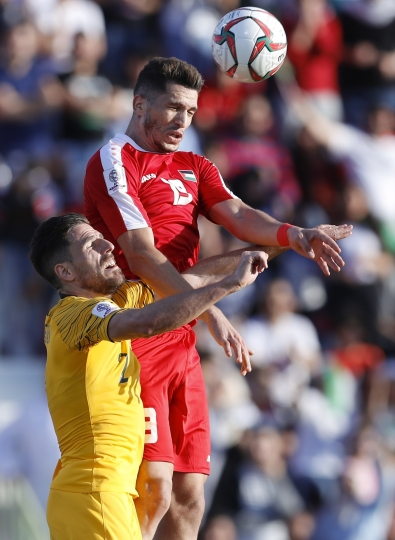 Palestine forward Mahmoud Wadi, top, and Australia defender Milos Degenek vie for the ball during the AFC Asian Cup group B soccer match between Australia and Palestine at Al Maktoum Stadium in Dubai, United Arab Emirates, Friday, Jan. 11, 2019. (AP Photo/Hassan Ammar)