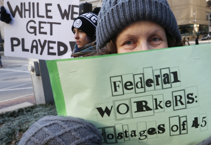 Esther Anastasia holds a sign during a protest rally with government workers and their supporters in Boston, Friday, Jan.11, 2019. The workers rallied with Democratic U.S. Sen. Ed Markey and other supporters to urge that President Donald Trump put an end to the shutdown so they can get back to work. (AP Photo/Michael Dwyer)
