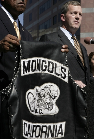 FILE - In this Tuesday, Oct. 21, 2008 file photo, U.S. Attorney Thomas P. O'Brien, right, speaks during a news conference in Los Angeles about the arrest of several Mongol motorcycle gang members in six states as a vest with the Mongols logo displayed. Federal prosecutors say a California jury has decided the Mongols motorcycle gang should be stripped of its trademarked logo. Jurors in U.S. District Court in Santa Ana on Friday, Jan. 11, 2018, found that the government could seize control of the group's trademark. The jury previously found the Mongol Nation, the entity that owns the image of a Mongol warrior on a chopper, guilty of racketeering and conspiracy. (AP Photo/Ric Francis, File)