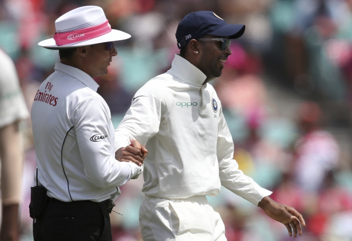 India's Hardik Pandya, right, shakes hands with umpire Richard Kettleborough after they collided while Pandya was fielding against Australia on day 3 of their cricket test match in Sydney, Saturday, Jan. 5, 2019. (AP Photo/Rick Rycroft)