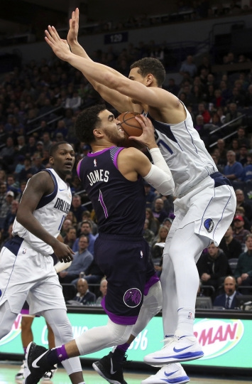 Minnesota Timberwolves' Tyus Jones, left, eyes the basket as Dallas Mavericks' Luka Doncic, of Slovenia, hovers over him in the first half of an NBA basketball game Friday, Jan. 11, 2019, in Minneapolis. (AP Photo/Jim Mone)