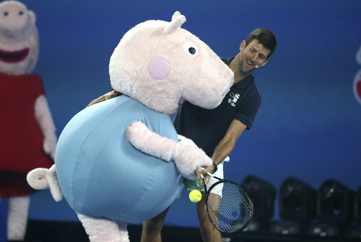 Serbia's Novak Djokovic and Peppa Pig combine to return a shot during Kids Tennis Day ahead of the Australian Open tennis championships in Melbourne, Australia, Saturday, Jan. 12, 2019. (AP Photo/Mark Schiefelbein)