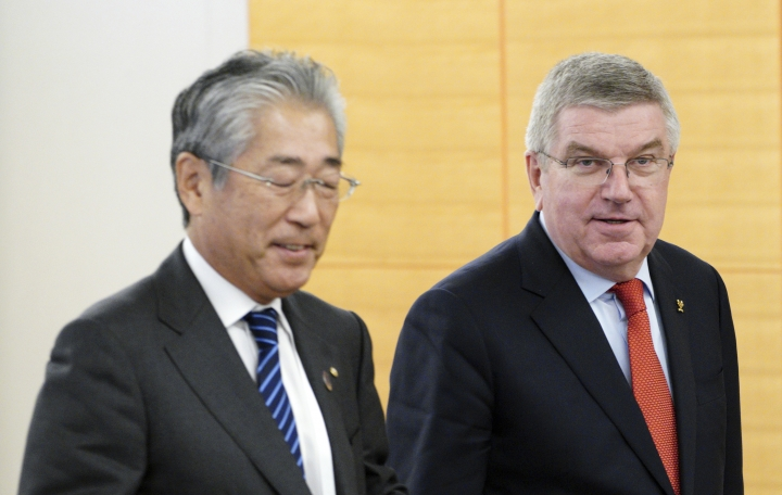 """FILE - In this Nov. 30, 2018, file photo, International Olympic Committee (IOC) President Thomas Bach, right, escorts Japanese Olympic Committee (JOC) President Tsunekazu Takeda during an IOC Executive Board meeting in Tokyo. France's financial crimes office says International Olympic Committee member Takeda is being investigated for corruption related to the 2020 Tokyo Olympics. The National Financial Prosecutors office says Takeda, the president of the Japanese Olympic Committee, was placed under formal investigation for """"active corruption"""" on Dec. 10.(AP Photo/Eugene Hoshiko, File)"""