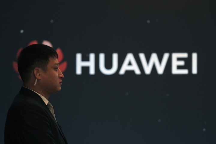 """In this Jan. 9, 2019, photo, a security guard stands near the Huawei company logo during a new product launching event in Beijing. The Chinese Foreign Ministry said late Friday, Jan. 11, 2019, it is """"closely following the detention of Huawei employee Wang Weijing"""" on charges of allegedly spying for China, and has asked Poland to """"handle the case lawfully, fairly, properly and to effectively guarantee the legitimate rights of the person, his safety and his humanitarian treatment,"""" according to state broadcaster CCTV. (AP Photo/Andy Wong)"""