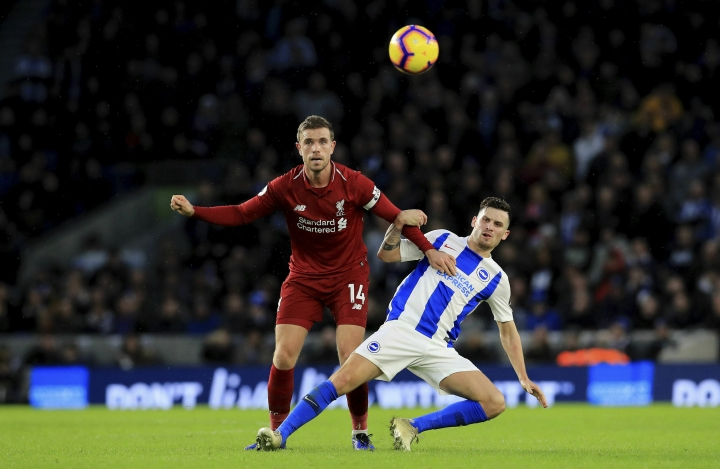 Liverpool's Jordan Henderson, left, and Brighton & Hove Albion's Pascal Gross battle for the ball during the English Premier League soccer match between Brighton and Hove Albion and Liverpool F.C at the Vitality Stadium, Brighton England. Saturday, Jan. 12, 2019. (Gareth Fuller/PA via AP)