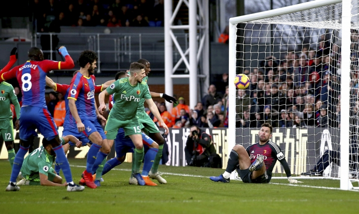 Watford goalkeeper Ben Foster, right, fails to make a save as team mate Craig Cathcart, center, scores an own goal during the English Premier League soccer match between Crystal Palace and Watford Town at the Selhurst Park stadium, London. Saturday, Jan. 12, 2019 (John Walton/PA via AP)