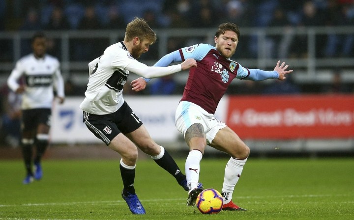 Fulham's Tim Ream, left, and Burnley's Jeff Hendrick battle for the ball during the English Premier League soccer match between Burnley F.C and Fulham at the Turf Moor stadium, Burnley, England. Saturday, Jan. 12, 2019. (Dave Thompson/PA via AP)