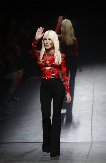 Donatella Versace acknowledges the audience's applause at the end of her men's Fall-Winter 2019-20 collection, that was presented in Milan, Italy, Saturday, Jan.12, 2019. (AP Photo/Antonio Calanni)