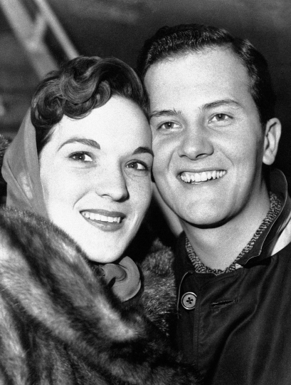 FILE - In this April 4, 1958 file photo, American singer Pat Boone and his wife Shirley are pictured at the London airport after their arrival from New York. Shirley Boone, the longtime wife of singer Pat Boone as well as a philanthropist, has died at age 84. Milt Suchin, Pat Boone's manager, says in a statement that Shirley Boone passed away on Friday, Jan. 11, 2019, surrounded by her four daughters, who sang to her. (AP Photo/File)