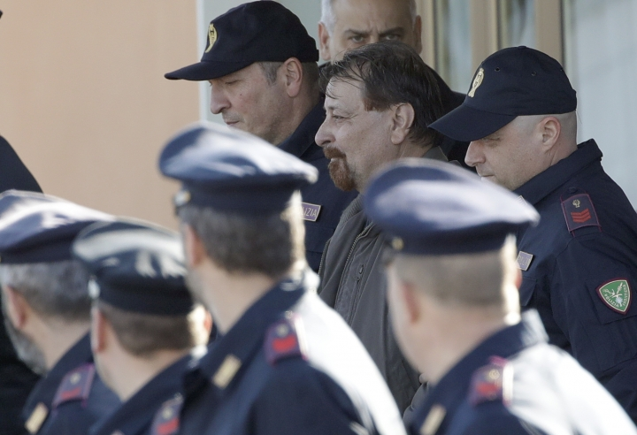 Italian fugitive Cesare Battisti is escorted by police as he leaves Ciampino military airport, in Rome, Monday, Jan. 14, 2019. Battisti escaped from an Italian prison in 1981 while awaiting trial on four counts of murder allegedly committed when he was a member of the Armed Proletarians for Communism. (AP Photo/Alessandra Tarantino)
