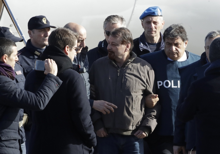 Italian fugitive Cesare Battisti, center, arrives at Ciampino military airport, in Rome, Monday, Jan. 14, 2019. Battisti a left-wing Italian militant who was convicted of murder three decades ago is heading home to serve a life sentence, after his life as a celebrity fugitive came to an abrupt end with his arrest in Bolivia by a team of Interpol agents. (AP Photo/Alessandra Tarantino)